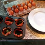 Put the bacon in the cups of a muffin pan.